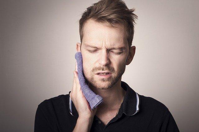 Hombre con dolor de muelas llevándose la mano al mentón