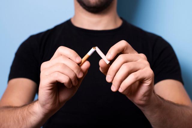 hombre rompiendo un cigarro en dos con las manos